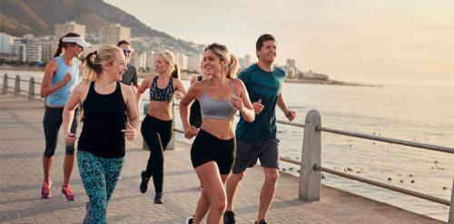 Grupo de atletas corriendo por un paseo marítimo